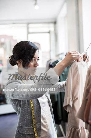 Mid adult female design professional analyzing dress in studio