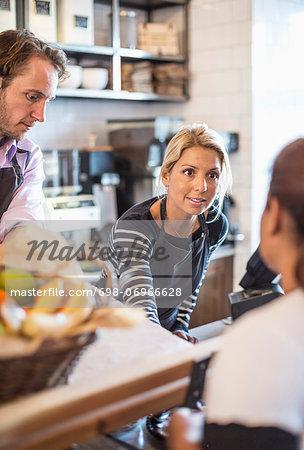 Female owner attending customer at counter in restaurant