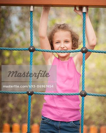Half-length shot of young girl on climbing net