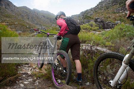 Young woman pushing mountain bike up mountain path