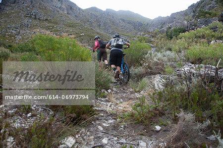 Young couple pushing mountain bikes up mountain