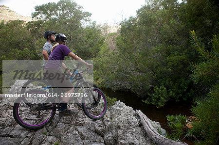 Young couple on mountain bikes on edge of rock