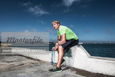 Young man in sportswear resting on pier