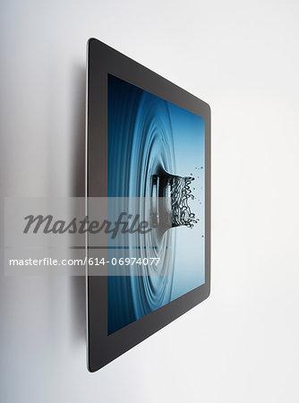 Digital tablet with crown shaped water drop splash on screen