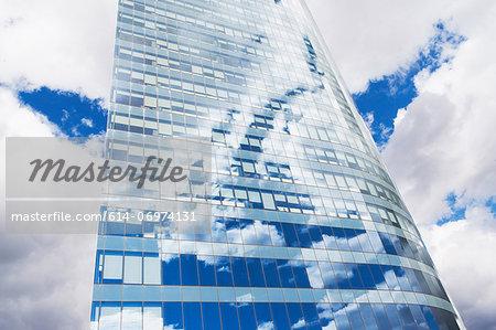 Blue cloudy sky reflected in modern skyscraper