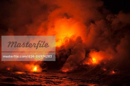 Smoke clouds from lava flow impacting sea at night, Kilauea volcano, Hawaii