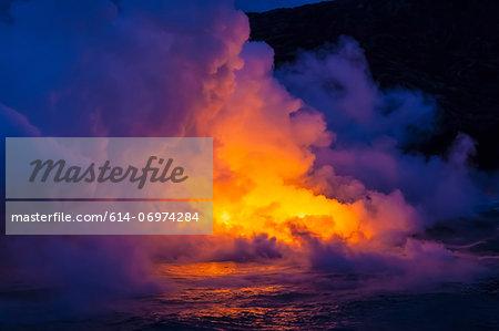 Smoke clouds from lava flow impacting sea at dusk, Kilauea volcano, Hawaii