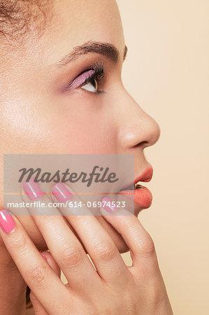 Side view of woman wearing make up and nail polish