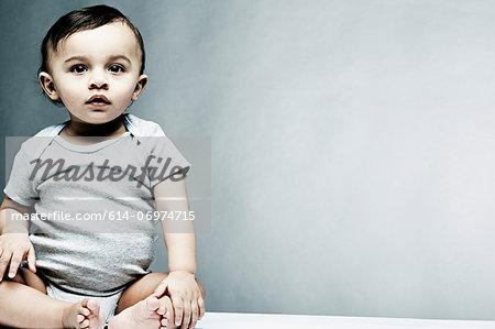 Portrait of baby boy wearing grey baby vest