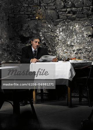 Senior businessman reading newspaper in restaurant