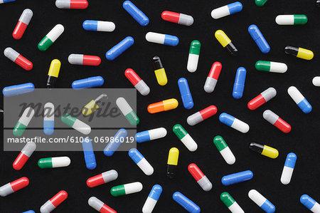 Coloured medicine capsules against black background