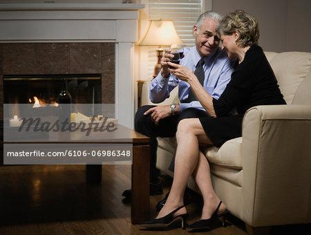 Senior couple sitting on sofa by fireplace, holding wine glasses