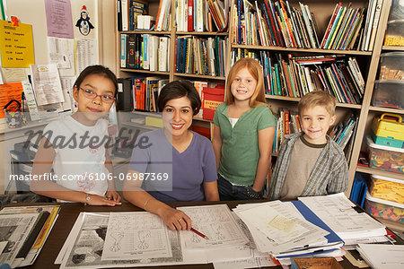 Teacher sitting at desk with three children (8-11), elevated view