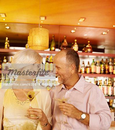 Flirtatious Couple Enjoying Cocktails in a Bar