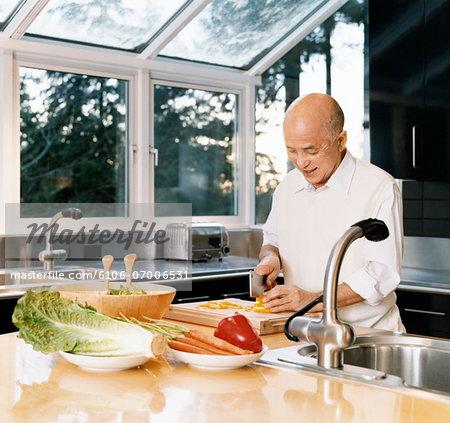 Senior Man Chopping Vegetables in a Kitchen