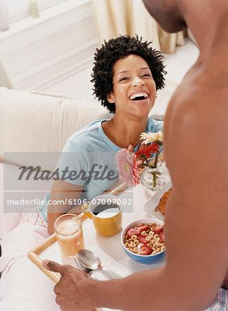 Man Giving a Woman Breakfast in Bed