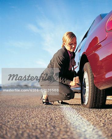 Businesswoman Repairing Her Punctured Tyre