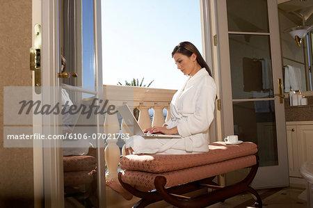 Woman wearing bathrobe using laptop