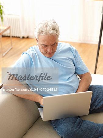 Mature man sitting on sofa, using laptop