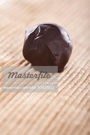 A home-made chocolate truffle coated in dark chocolate