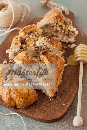 Hazelnut Roll Sliced on a Board with a Honey Dipper