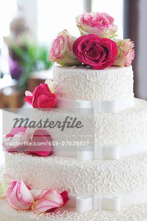An elegant wedding cake decorated with fresh roses