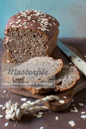 Partially Sliced Gluten Free Whole Grain Bread on a Cutting Board