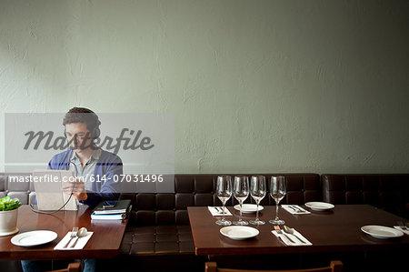 Young man wearing headphones in restaurant