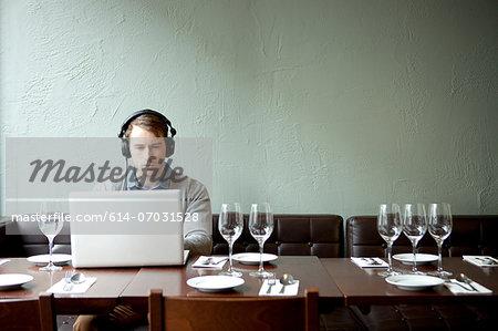 Young man wearing headphones using laptop in restaurant