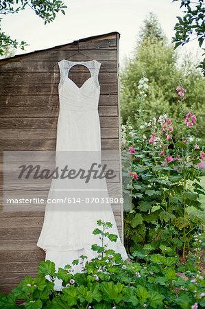 Wedding dress hanging on garden shed