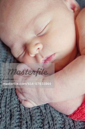Baby boy lying on grey blanket, sleeping
