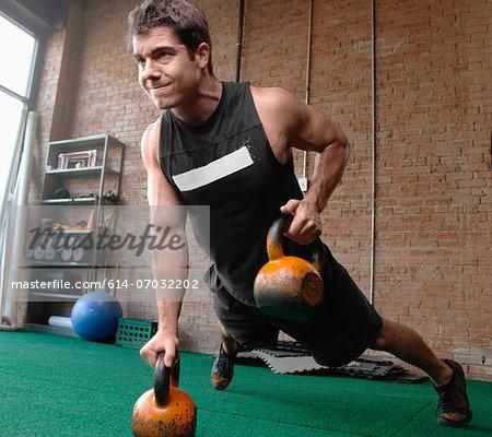 Male bodybuilder lifting kettlebells