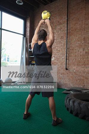 Male bodybuilder lifting kettlebells in gym