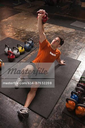 Bodybuilder lifting kettlebell in gym