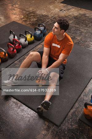 Bodybuilder resting on exercise mat in gym