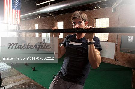 Bodybuilder pulling up on bar in gym