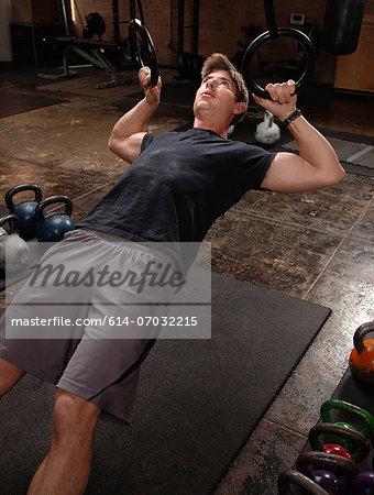 Bodybuilder on floor in gym using rings