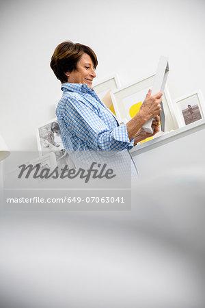 Senior woman holding family photographs