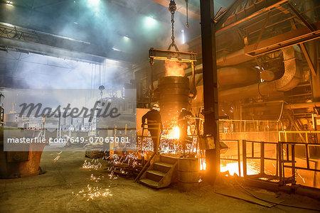 Steel workers watching furnace in steel foundry