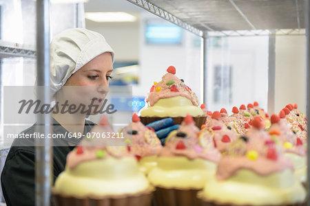 Chocolatier arranging giant chocolate cupcakes in sweet factory