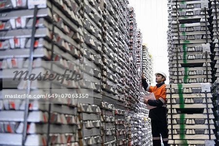 Warehouse worker checking stacked aluminum ingots