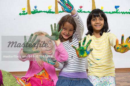 Three girls kneeling on floor with painted hands