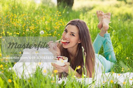 Woman in field of buttercups eating fresh fruit