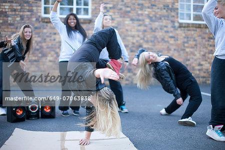 Blond girl breakdancing in playground