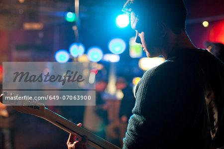 Man on stage playing guitar in nightclub