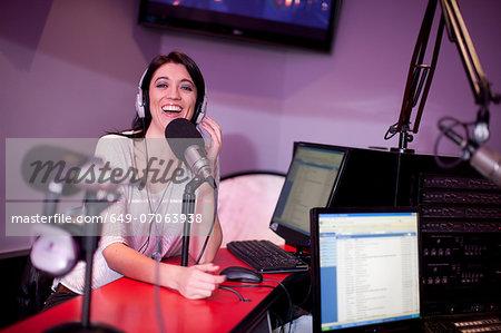 Mid adult woman broadcasting in recording studio, portrait