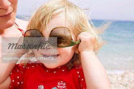 Baby girl wearing sunglasses upside down