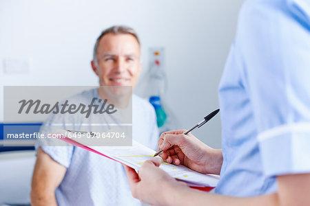 Nurse completing paperwork, patient in background