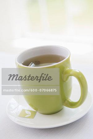 Cup of Tea in Green Mug with Saucer, Studio Shot