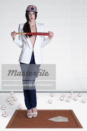 Portrait of young woman holding baseball bat, studio shot on white background